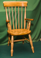 Child size backed chair with arms.