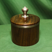 Lidded box in Rosewood with pewter rim and finial.