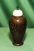 Lidded vessel in black and gold with contrasting lid and ebony finial.