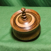 Lidded box in walnut with contrasting onlay on the lid plus finial.